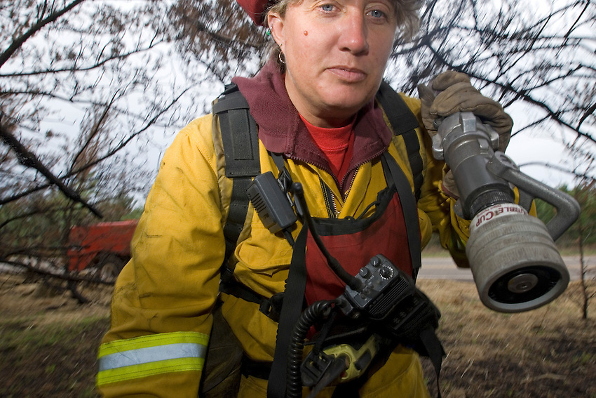Portrait of female fire fighter with Michigan Department of Natural Resources wildfire crew at site of forest fire in Michigan Upper Peninsula.