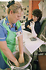 Female patient having plaster cast on broken arm replaced by staff nurse in fracture clinic of hospital,