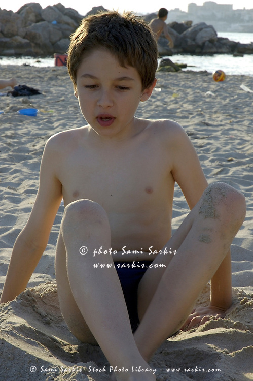 Young boy sitting at the beach.