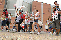 Phoenix, Arizona. April 25, 2012 - Demonstrators walk in front of the Maricopa County Fourth Avenue Jail as part of a march organized to oppose SB 1070. About 500 people protested the controversial law on the same day U.S. Supreme Court justices heard legal arguments on the Arizona vs. United States case. At the end of the march, six activists blocked Central Avenue by sitting in the middle of the street. They all were arrested by the Phoenix Police Department and taken to the Fourth Avenue County Jail. Photo by Eduardo Barraza © 2012