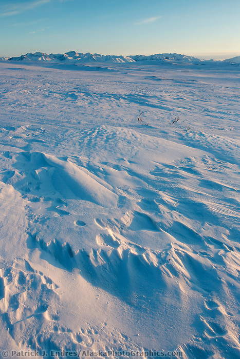 Wind blown snow patterns with the Brooks Range mountains in the distance, Arctic, Alaska.