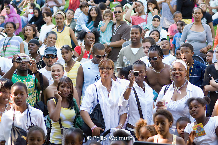 A crowd of local residents watch performances at Queens Park Gardens summer festival, West London