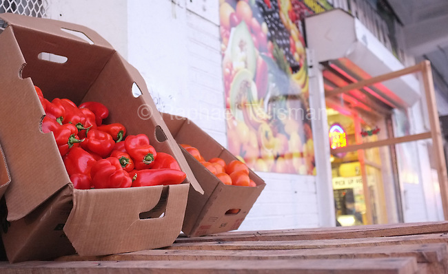 Fresh red peppers and tomatoes are on display outside of a Mexican produce store at the Florida Avenue Market in early December