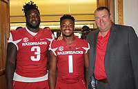 NWA Democrat-Gazette/CARIN SCHOPPMEYER McTelvin Agim, defensive lineman (from left), Chevin Calloway, defensive back, and Bret Bielema, Arkansas Razorbacks head football coach gather at the Arkansas Football Kickoff Luncheon on Aug. 18 at the Northwest Arkansas Convention Center in Springdale.