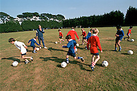 Schoolchildren playing football during their sports lesson in the school playing fields. They are being instructed by a PE teacher. This image may only be used to portray the subject in a positive manner..©shoutpictures.com..john@shoutpictures.com