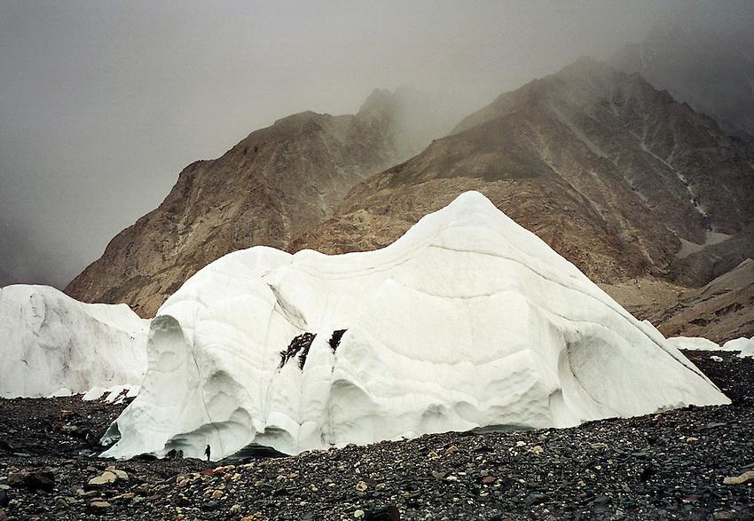 On the Baltoro glacier, the trek leading to K2 basecamp, the world's second highest mountain, a trekker stop below a huge ice block. Karakoram mountain range, Baltistan, Pakistan.