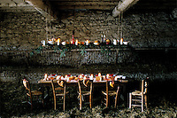 A festive table in a hay-strewn barn alight with candles and decorated in red and white with bread hearts hanging from the chairs