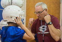NWA Democrat-Gazette/ANTHONY REYES &bull; @NWATONYR<br /> David Reed, head coach for the J.O. Kelly football team, helps Pedro Castro, 12, with his helmet Friday, Aug. 21, 2015 at J.O. Kelly Middle School in Springdale. The seventh-graders who signed up for football were fitted for football jerseys and other equipment. All the middle school's in the district will have seventh grade teams. This is the first year for Springdale School District to offer seventh-grade sports.