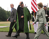 Camp David, MD - August 5, 2007 -- President Hamid Karzai of Afghanistan talks to first lady Laura Bush as they walk towards VIP golfcarts during an arrival ceremony at Camp David, Maryland on Sunday, August 5, 2007.  United States President George W. Bush looks on from the left..Credit: Dennis Brack - Pool via CNP