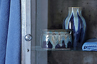 A metal former dentist's cabinet in the bathroom now displays a pair of blue glazed pots
