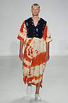Model walks runway in an African orange/indigo mud cloth kaftan from the Palmiers du Mal Spring Summer 2017 collection by Brandon Capps and Shane Fonner, at Skylight Clarkson Square on July 14 2016, during New York Fashion Week Men's Spring Summer 2017.