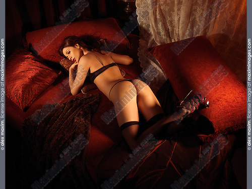 Glamour photo of a sexy young woman in black lingerie lying on a bed