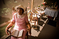 An elderly african-american woman sits in her rocking chair singing gospel tunes with her bible on her lap.
