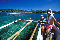 Man in outrigger canoe with another boat, in clear blue water, Siargao Island, Philippines