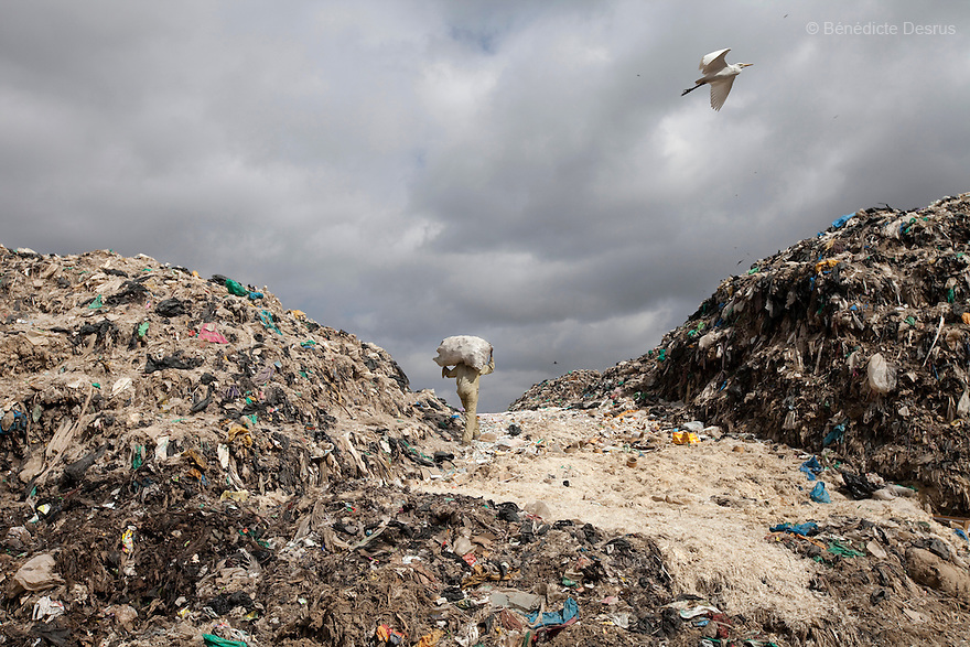 2013 - Dandora dumpsite, Nairobi, Kenya - A Kenyan man lifts a sack of recyclable materials at the Dandora dumpsite, one of the largest and most toxic in Africa. Located near slums in the east of the Kenyan capital Nairobi, the open dump site was created in 1975 and covers 30 acres. The site receives 2,000 tonnes of unfiltered garbage daily, including hazardous chemical and hospital wastes. .It is a source of survival for many people living in the surrounding slums, however it also harms children and adults' health in the area and pollutes the Kenyan capital. Photo credit: Benedicte Desrus