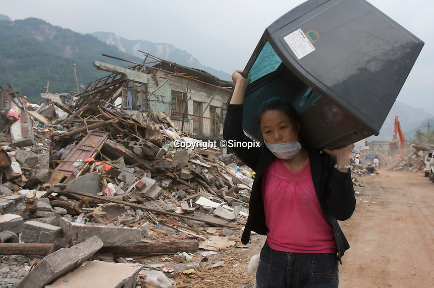 A woman takes her funiture back after the deadly earthquake. The 8 magnitude earthquake happened at 14:28pm on 12 May 2008, with the epicenter in Wenchuan County, about 159km NW of Chengdu, Sichuan, China..20 May 2008