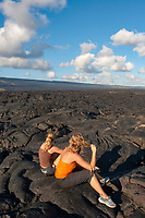 two women hikers, resting at the fresh lava field, Chain of Crater Road, Hawaii Volcanoes National Park, Kilauea, Big Island, Hawaii, USA, Pacific Ocean