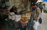 Palestinian men bake bread in a traditional mud oven in the West Bank city of Nablus, on February 17, 2019. Photo by Shadi Jarar'ah