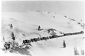 Rotary snowplow OM trailed by 4 light engines and assorted outfit cars.<br /> D&amp;RGW  Cumbres, CO  circa 1920