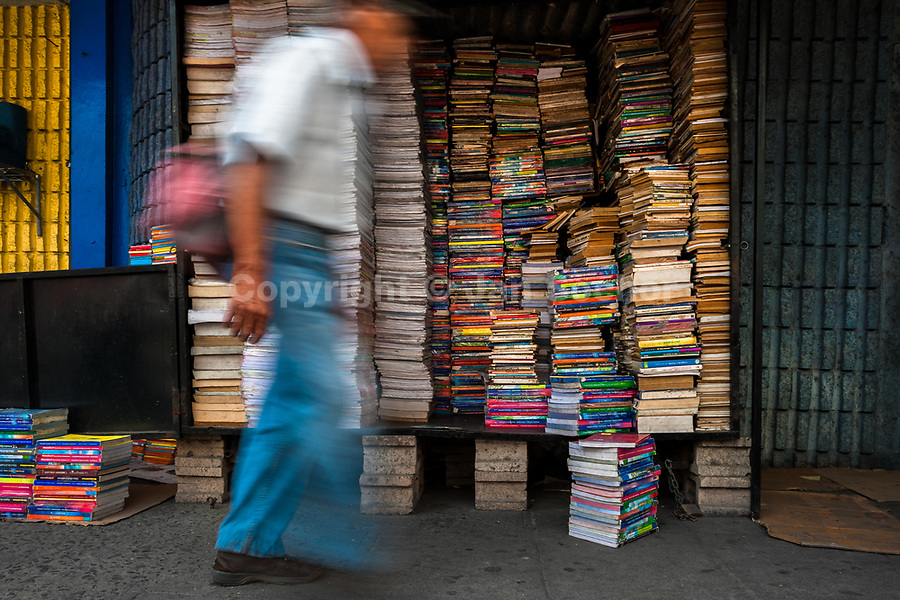 A Salvadoran man walks in front of piles of used books stacked in a box on the street in a secondhand bookshop in San Salvador, El Salvador, 11 April 2018. Large collections of worn-out books, mostly textbooks and educational paperbacks, are sold regularly in secondhand bookshops in the center of the city.