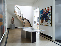 In the entrance hall the walls are finished in marmorino plaster and features marble floors and a gently curved wrought-iron staircase railing. The table is a 1970s design by Maria Pergay, the painting at right is by Joan Mitchell, the one on the opposite wall is by Sean Scully, and the sculpture is by Ugo Rondinone.