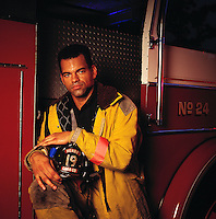 Portrait of a Black male firefighter in uniform seated on a firetruck.