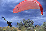 A paraglider pilot begins his launch off Chelan Butte in Chelan, Washington.