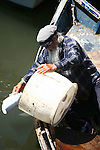 Whiskered old man in panga boat about to empty water into harbor.<br />