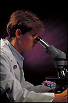 Lab technician looking through microscope