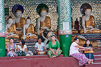 Myanmar, Burma.  Shwedagon Pagoda, Yangon, Rangoon.  Women Resting, Eating Snacks, on Steps of a Courtyard Shrine.  Behind them Buddha Statues  demonstrate the mudras (hand gestures) of earth-touching (bhumisparsha) and wisdom (dhyana).