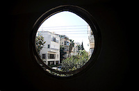 A view through a circular window of the Bauhaus style buildings on Rehov Gezer Street. Tel Aviv is known as the White City in reference to its collection of 4,000 Bauhaus style buildings, the largest number in any city in the world. In 2003 the Bauhaus neighbourhoods of Tel Aviv were placed on the UNESCO World Heritage List. ..