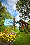 Rustic log cabin building of K2 Aviation surrounded by flower pots, Talkeetna, Southcentral Alaska, Summer.