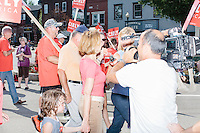 A CNN reporter tries to ask a question of Republican presidential candidate Carly Fiorina as she marches in the Labor Day parade surrounded by supporters in Milford, New Hampshire. Fiorina would not answer any questions during the parade. Republican candidates John Kasich, Carly Fiorina, and Lindsey Graham, and Democratic candidate Bernie Sanders marched in the parade.