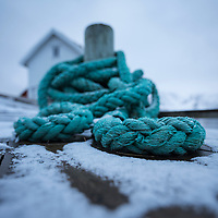 Coil of rope on pier in winter, Moskenesøy, Lofoten Islands, Norway