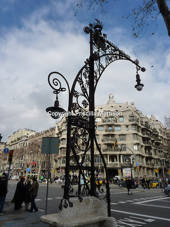 Barcelona, Spain - January 30, 2011:  An ornate street light stands across Passeig de Gracia from Casa Mila.