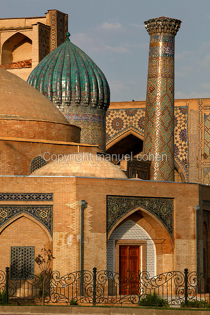 """Detail of dome and minaret of the Sher-Dor Madrasah, seen from the Chorsu, dome-arched construction, 1619-36, Registan, Samarkand, Uzbekistan, pictured on July 16, 2010, in the afternoon. The Sher-Dor Madrasah, commissioned by Yalangtush Bakhodur as part of the Registan ensemble, and designed by Abdujabor, takes its name, """"Having Tigers"""", from the double mosaic (restored in the 20th century) on the tympans of the portal arch showing suns and tigers attacking deer. Samarkand, a city on the Silk Road, founded as Afrosiab in the 7th century BC, is a meeting point for the world's cultures. Its most important development was in the Timurid period, 14th to 15th centuries. Picture by Manuel Cohen."""