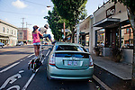 """Michael Jones, a """"transportationalist"""" who owns six bicycles and 5 unicycles, rides his """"tall bike"""" with girlfriend Evelyn Barnes riding on the back in Portland's Kenton neighborhood.  A tall bike consists of one bicycle frame welded on top of another with vertical and horizontal chain drives and a seat six feet above the ground."""