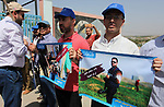 Palestinian journalists hold posters depicting a Palestinian photographer Yasser Qudih, who was wounded on 14 May by Israeli troops as he covering a demonstration where Palestinians demand their rights to return to their home at Israel-Gaza border, at Erez crossing, in the northern Gaza Strip, before he return from Makassed hospital in Jerusalem where he was recovering on May 27, 2018. Photo by Mahmoud Ajour