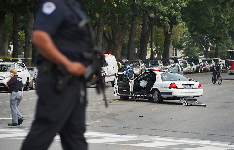 UNITED STATES - OCTOBER 03: A U.S. Capitol Police officer stands guard near a police car after a shooting and subsequent police car crash on Constitution Avenue and 1st. Street, NW. The officer was injured in the car crash. (Photo By Tom Williams/CQ Roll Call)