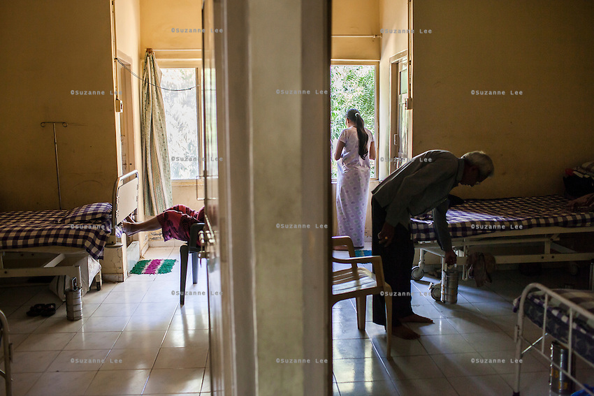 Surrogates pass their time talking on their mobile phones or watching the happenings outside through their windows in the surrogates hostel on the 3rd floor of Dr. Nayana Patel's Akanksha IVF and surrogacy center in Anand, Gujarat, India on 11th December 2012. Photo by Suzanne Lee / Marie-Claire France