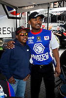 May 17, 2014; Commerce, GA, USA; A young fan poses with NHRA top fuel dragster Antron Brown during qualifying for the Southern Nationals at Atlanta Dragway. Mandatory Credit: Mark J. Rebilas-USA TODAY Sports
