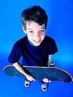 Smiling wholesome teenage boy holding his skate board