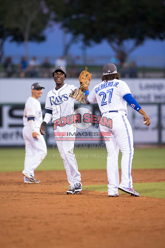 AFL West shortstop Lucius Fox (5), of the Peoria Javelinas and the Tampa Bay Rays organization, is congratulated by Vladimir Guerrero Jr. (27) after making a play during the Fall Stars game at Surprise Stadium on November 3, 2018 in Surprise, Arizona. The AFL West defeated the AFL East 7-6 . (Zachary Lucy/Four Seam Images)