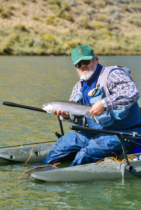 Fly fisherman land large rainbow trout. Pond in Freemont National Forest, Oregon