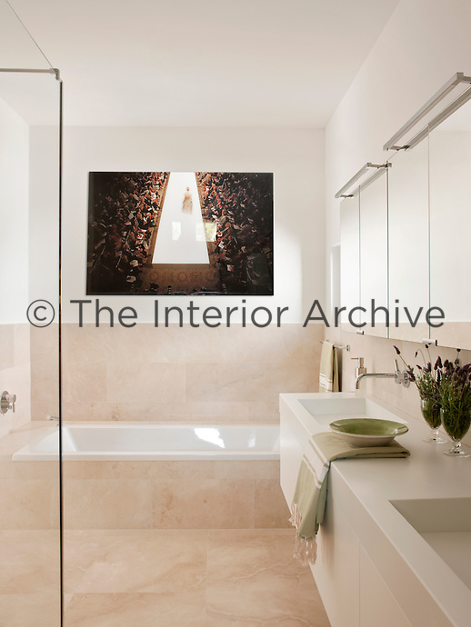 A contemporary bathroom in neutral tones. A mirrored wall cabinet is placed above two washbasins set in a cupboard unit. A photograph by Philipp Hoffmann hangs above a built-in bath. The floor is of sand-blasted stone, which also extends halfway up the walls.