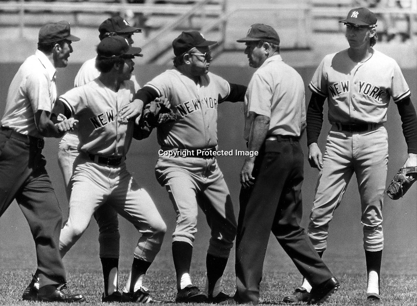 New York Yankee manager Ralph Houk holds back Roy White while in argument with umpire Jim Odom. in the first inning of game against the Oakland 's. (1973 photo by Ron Riesterer)