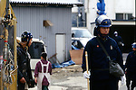 April, 1995, Kamikuisshiki Mura, Japan - A member Aum wearing a headgear walks behind a riot police trooper during a raid on the cult's facility - No. 2 Satyam - on the foot of Mt. Fuji in April 1995. Police found explosives, chemical weapons and biological warfare agents and a Russian Mil Mi-17 military helicopter. On the morning of 20 March 1995, Aum members released sarin in a coordinated attack on five trains in the Tokyo subway system, killing 13 commuters, seriously injuring 54 and affecting 980 more. Some estimates claim as many as 6,000 people were injured by the sarin. (Photo by Haruyoshi Yamaguchi/AFLO)