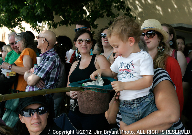 Three-year-old Dante Morris stuffs money in a hat while attending the 25th  Annual Fremont Summer Solstice Parade in Seattle on June 22, 2013.    UPI Photo/Jim BryantPainted nude bicyclists  ride during the 25th  Annual Fremont Summer Solstice Parade in Seattle on June 22, 2013.     ©2013.  Jim Bryant.  ALL RIGHTS RESERVED.