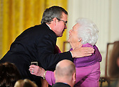 """Former first lady Barbara Bush prepares to kiss her son, former Florida Governor Jeb Bush prior to the ceremony where United States President Barack Obama and first lady Michelle Obama honored recipients of the 2010 Medal of Freedom, """"the Nation's highest civilian honor presented to individuals who have made especially meritorious contributions to the security or national interests of the United States, to world peace, or to cultural or other significant public or private endeavors"""", in a ceremony in the East Room of the White House in Washington, D.C. on Tuesday, February 15, 2011..Credit: Ron Sachs / CNP"""