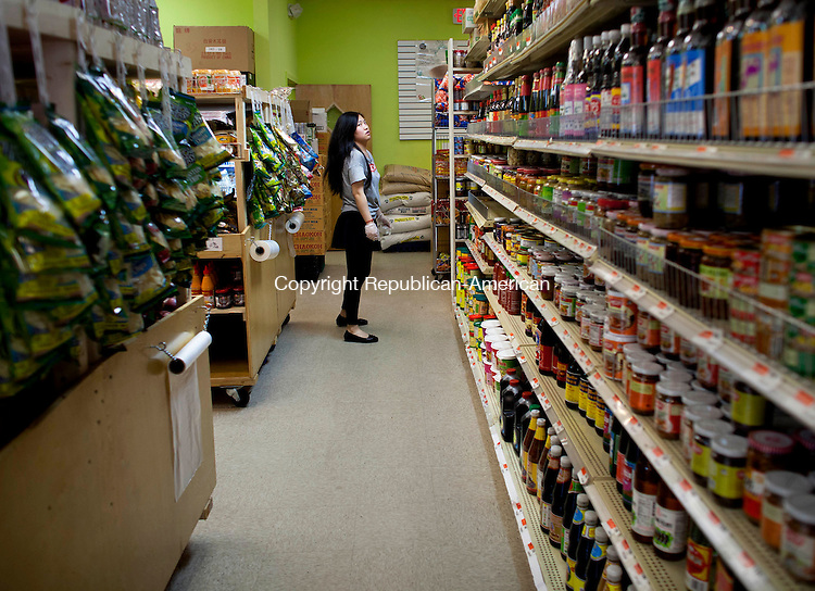 WATERBURY, CT- 10 June 2014-061014BF01- Zhihong Ma looks at the inventory inside the AAA Asian Market on Meriden Road in Waterbury Tuesday afternoon. The market caters to the asian community. Bob Falcetti Republican-American